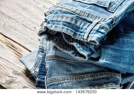 Blue jeans on Brown wooden background.Raw denim texture and close up on Dark background