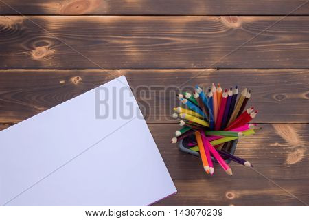 Pencils and album on a dark wooden table top view