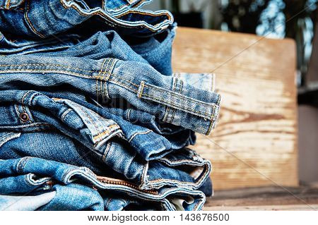 Pile of Old Indigo Jeans Denim on Wooden Table Background Texture