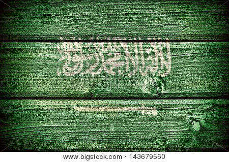 Flag of Saudi Arabia painted on old grungy wooden background: 3d illustration