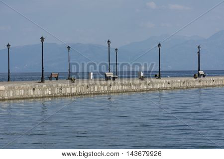 The seafront lined with stones on a background of mountains in the gray light with benches and lights along the pier