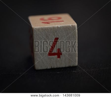 Wooden cube with the number four on a black