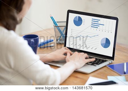 Young Office Woman Browsing Data On Laptop. Closeup