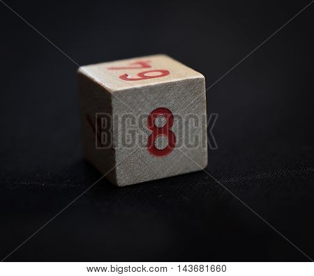 Wooden cube with the number eight on a black