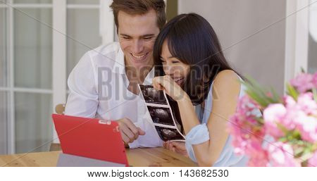 Happy couple showing off ultrasound pictures