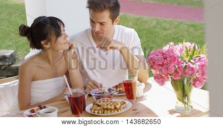 Couple talking at breakfast table outside