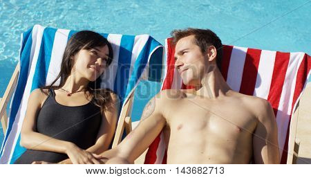 Contented young couple smiling as they sunbathe