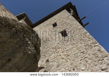 old fortress wall of grey rock sticking out of the rock a Sunny day on blue sky background