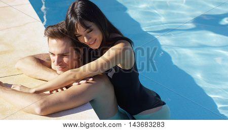 Woman in black swim suit hugs her boyfriend