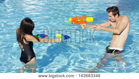 Happy couple shooting off water guns in pool