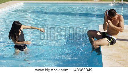 Girlfriend splashing her boyfriend at pool