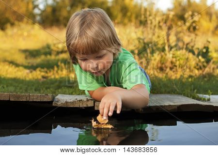 boy play with autumn leaf ship in water