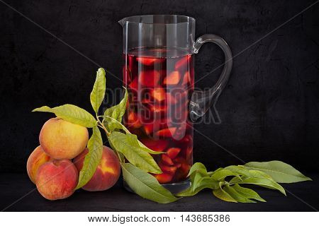 Pitcher with sangria and fresh peaches on black background with copy space.