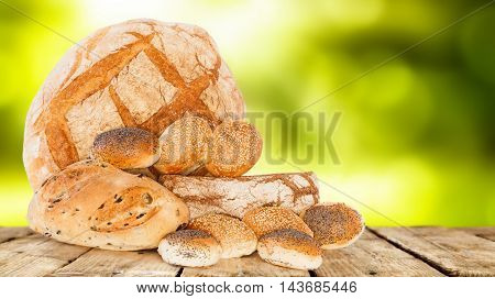 Mix of Italian breads fresh baked on old wooden table.