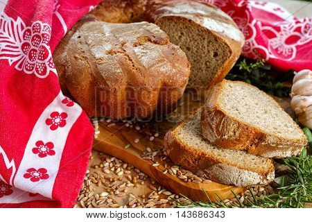 Freshly baked sourdough spelt bread on olive wood board with whole grains