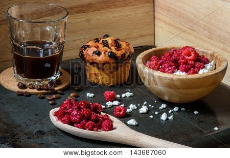 Cottage cheese with raspberries, coffee in a cup and blueberry muffin for breakfast with scattered berries, grains of curd and coffee beans