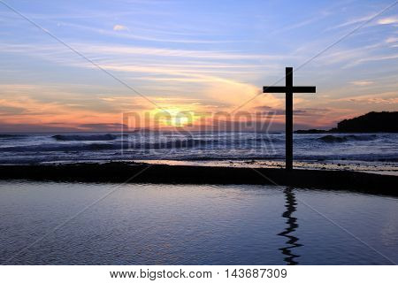 A Christian cross on the beach at sunset.