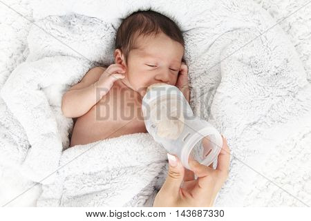 Newborn baby drinking milk from a bottle.