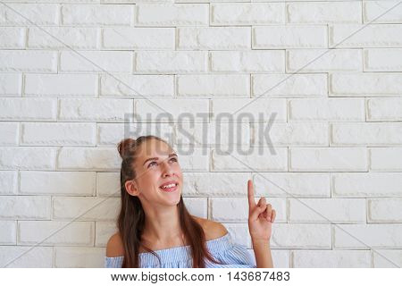 The moment when girl jumps up and down at the splendid idea, sitting on the floor and posing against white background
