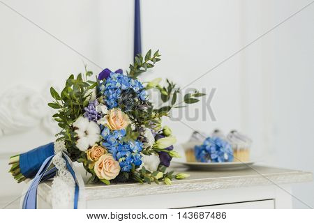 Wedding decorations with bride's bouquet, candle and cupcakes. blue and serenity, focus on bride's bouquet