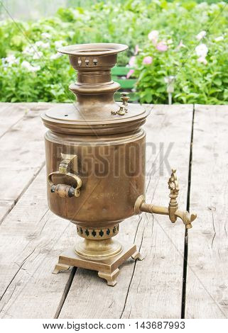 brass old samovar on a wooden table outdoor