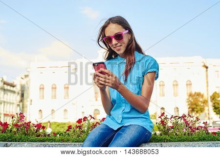 Beautiful teenage girl in pink sunglasses is sitting on flowerbed in historical part of the city and using her smartphone