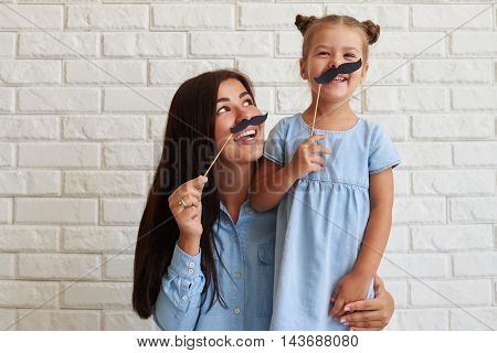 Horizontal close-up portrait of joyful and laughing family of young mother and her cute daughter in casual light-blue outfit holding paper moustache on sticks