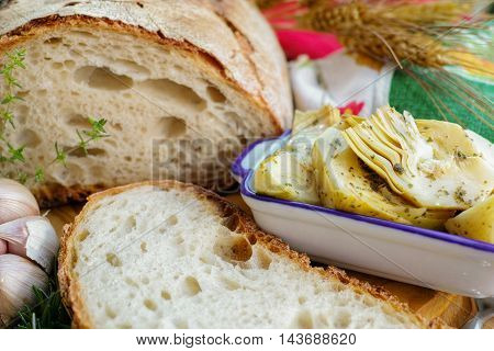 Homemade fresh italian bread and artichokes in brine with spices and herbs on wooden background