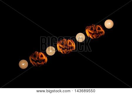 Three pumpkins and four candles in a dark background