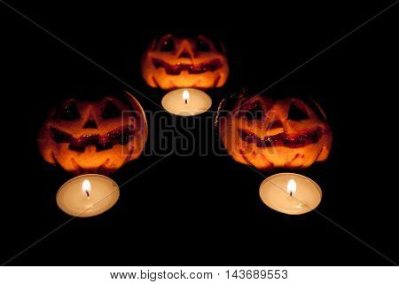 Three pumpkins with three candles in a dark background