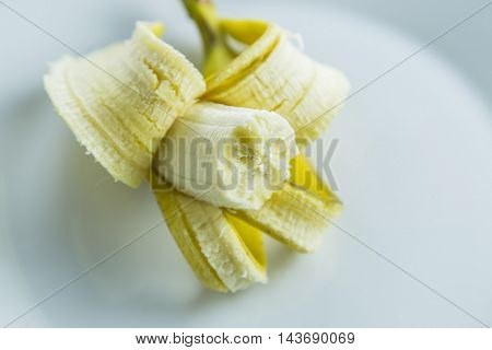 Bananas in plate on brown wooden background