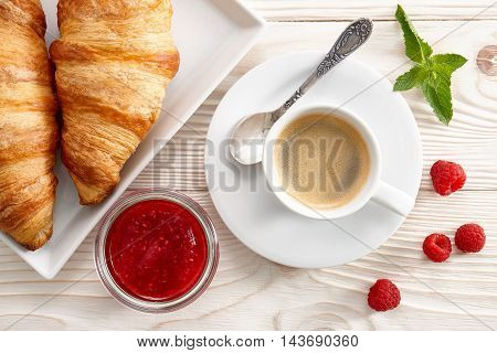 Morning breakfast with espresso coffee, raspberry jam and fresh croissants.