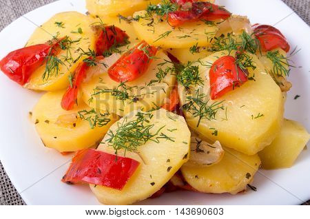 Closeup view of a vegetarian dish of natural ingredients - slices of stewed potatoes and bell pepper on a sackcloth background