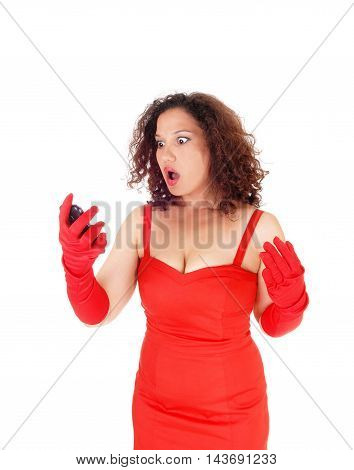 A beautiful young woman looking very surprised at her cell phone standing in a red dress isolated for white background.