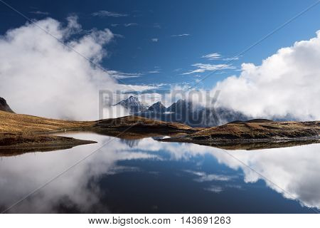 Highland Lake. Mountain landscape with tops and clouds. Reflection of the sky in water. Beauty in nature. Main Caucasian ridge. Koruldi lake, Zemo Svaneti, Georgia