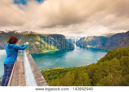 Tourism vacation and travel. Woman tourist taking photo with camera enjoying Aurland fjord view from Stegastein viewpoint Norway Scandinavia.