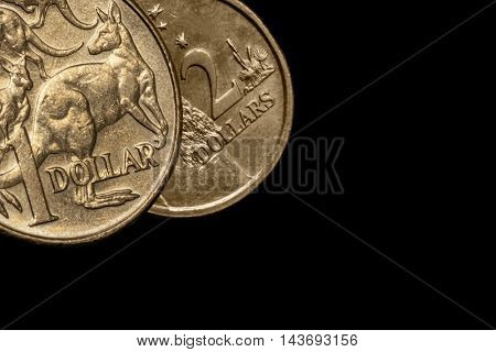 Australian one and two dollar coins over black background.
