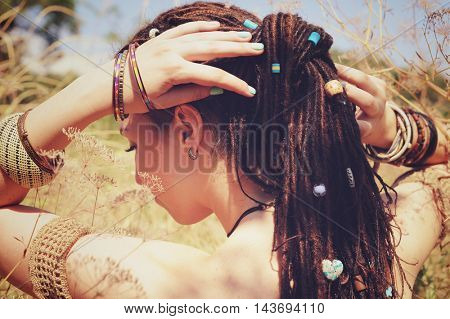 Beautiful young woman wearing dreadlocks hairstyle gathered in a ponytail and decorated assorted beads, autumn outdoor, focus on a hair