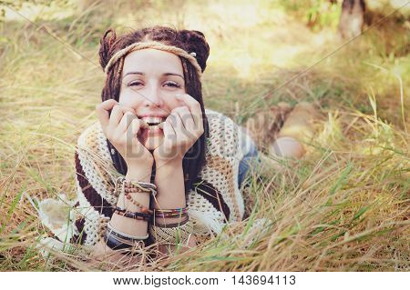 Boho style smiling woman portrait, girl have a fun lying outdoor in autumn sunny park, natural lifestyle concept