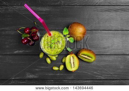 Fruit smoothie drink cocktail of kiwi cherries and grapes in glass. Ingredients fresh fruits for smoothie on dark wooden background cherry kiwi grapes Melissa leaves. Top view.