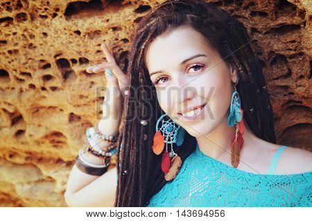 Portrait of a young smiling woman wearing dreadlocks hairstyle, dressed in blue lace dress and blue boho chic dreamcatcher earrings with leather feathers, posing against stone, looking at camera