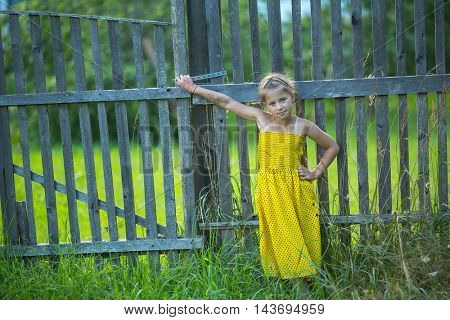 Little girl standing near fence in the village.