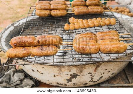 Display for sell BBQ with fiery sausages on the grill