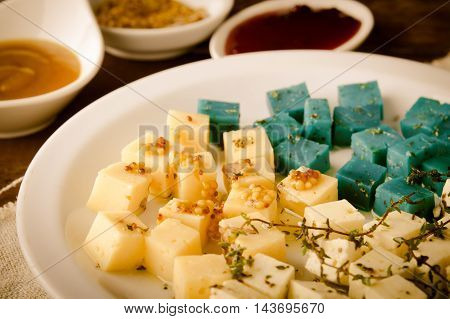 Cheese platter, variety of Gouda, feta, blue pesto cheeses on white plate with herbs, olive oil, thyme, pomegranate and mustard sauces