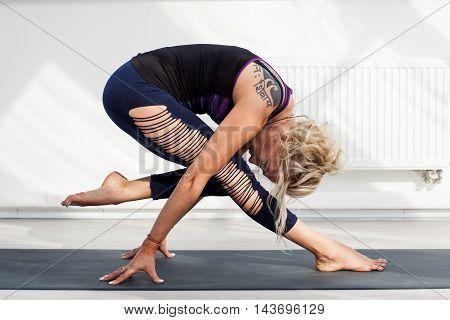 Blonde adult woman performing yoga asana in gim