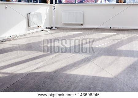 The floor in a room with the sunlight from the windows