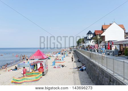 SARBINOWO - AUGUST 20: Tourists enjoy the sunny weather and relaxing on the Baltic sea beach on 20 August 2016 in Sarbinowo, Poland.