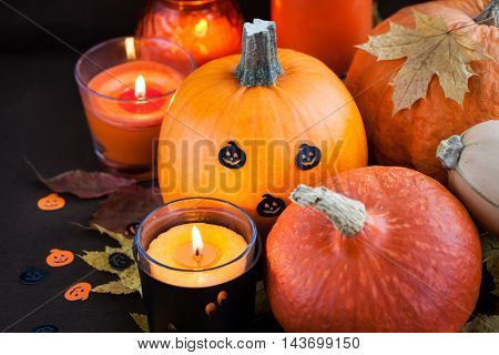 Decorative halloween pumpkins and candles on dark