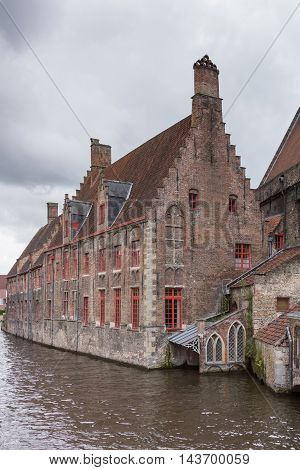 Brugge Belgium - August 10 2016: Medieval Sint Jans Hospital building along canal in Bruges. Rainy skies and dark canal water.