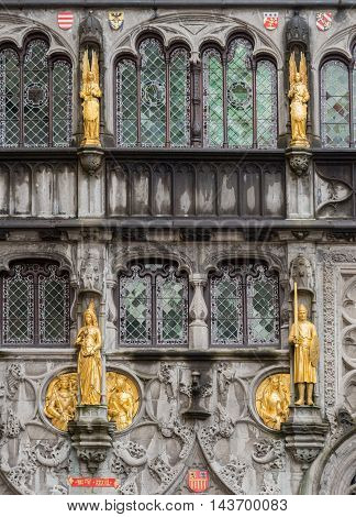 Brugge Belgium - August 10 2016: Detail of the gray and decorated facade of the Holy Blood Church in Bruges features golden statues of angels princes knights queens and kings.